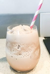 A bubbly chocolate smoothie with a pink and white straw.