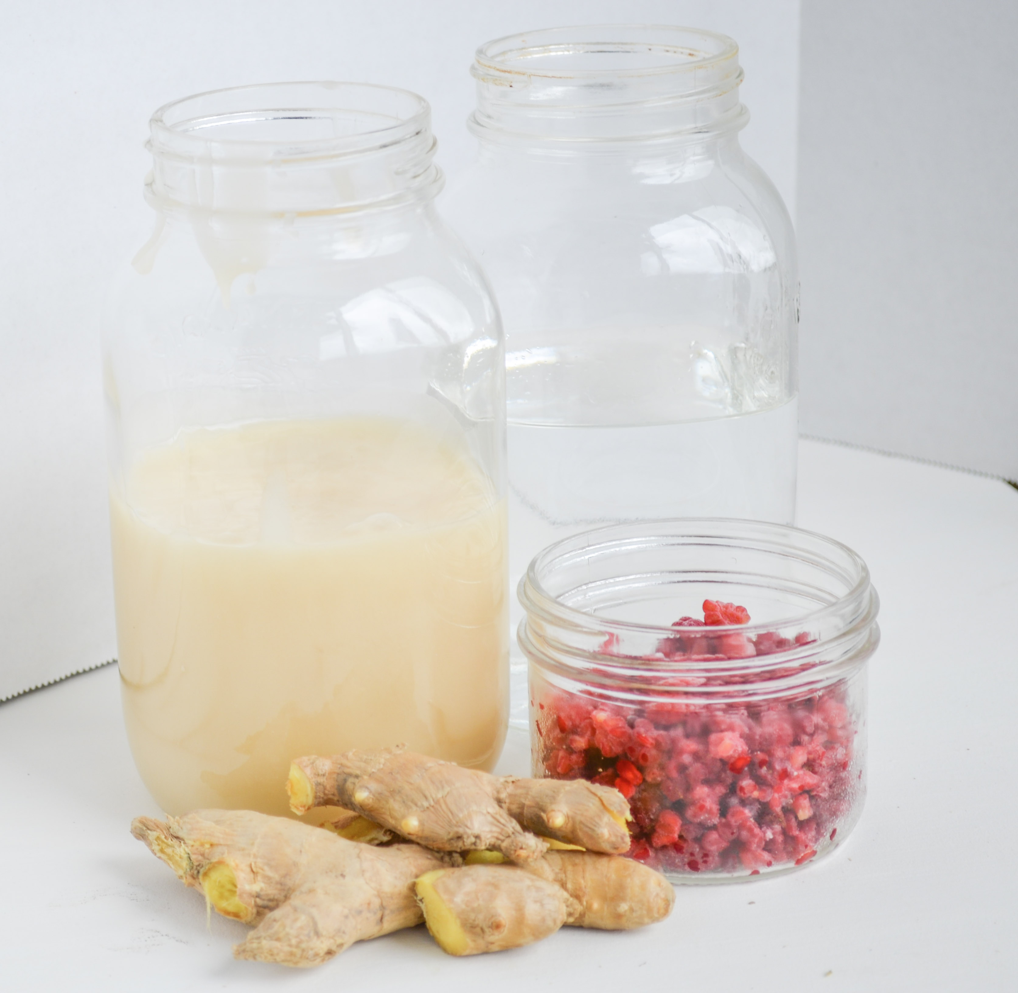 Mason jars with honey, raspberries and water, sitting next to ginger root.