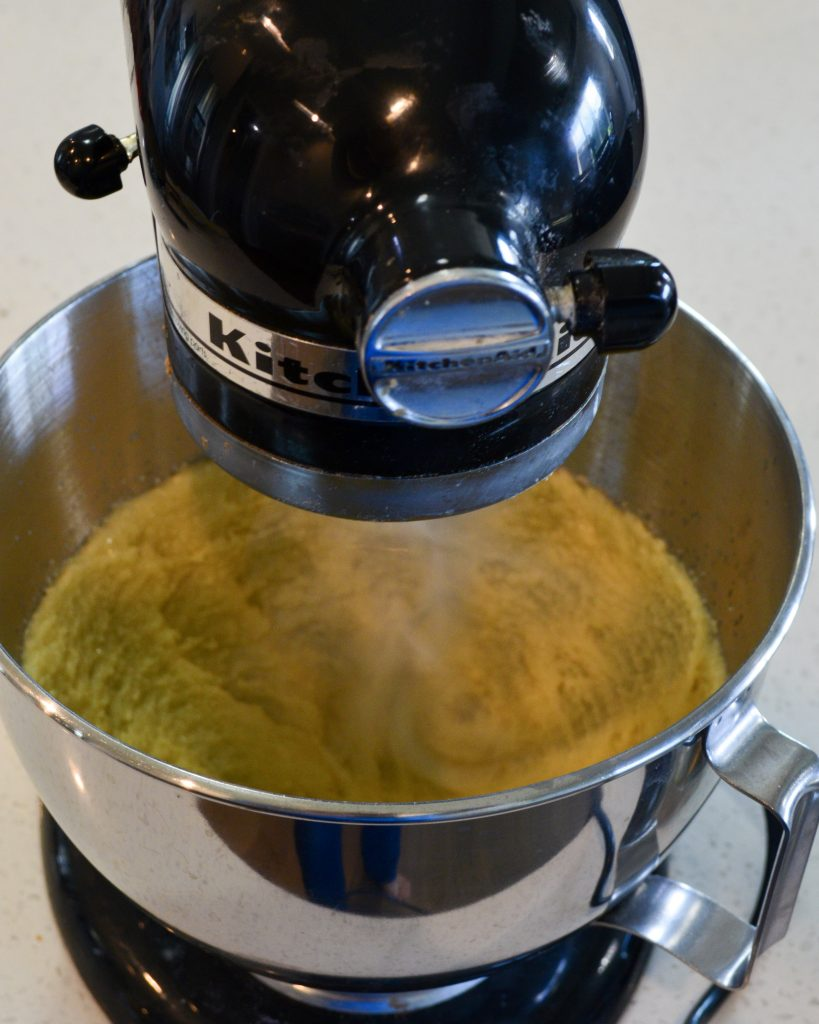 Black kitchen aid mixer creaming butter and sugar.