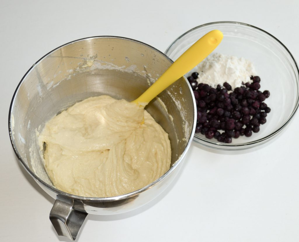 Silver mixer bowl with batter and a clear bowl of blueberries and flour.