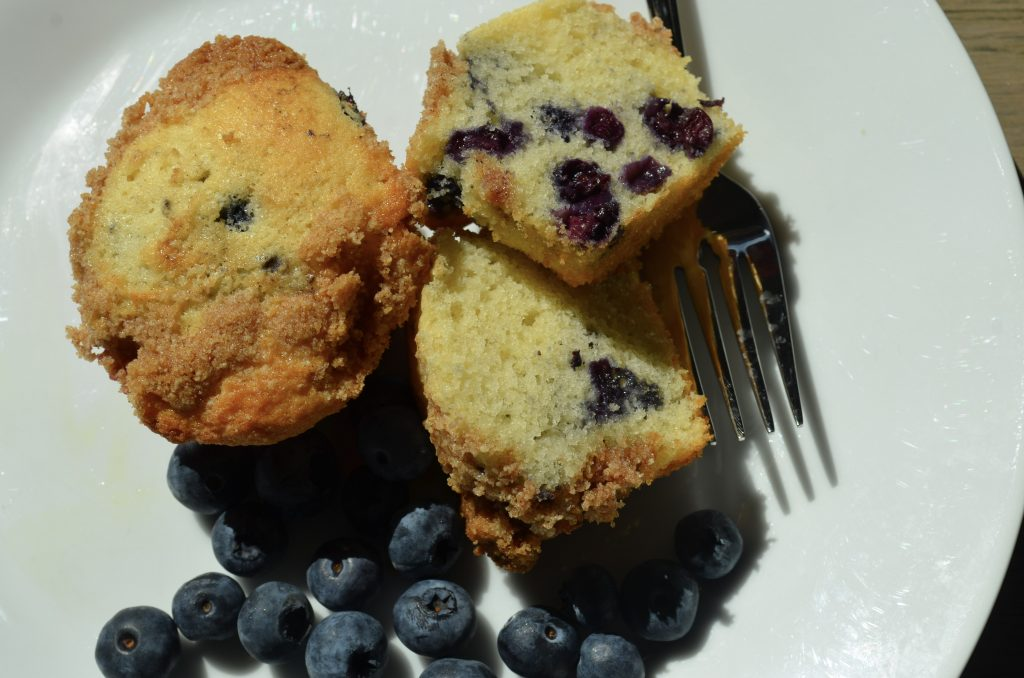 Whole muffin and two muffin halves with blueberries and delicious crumble.