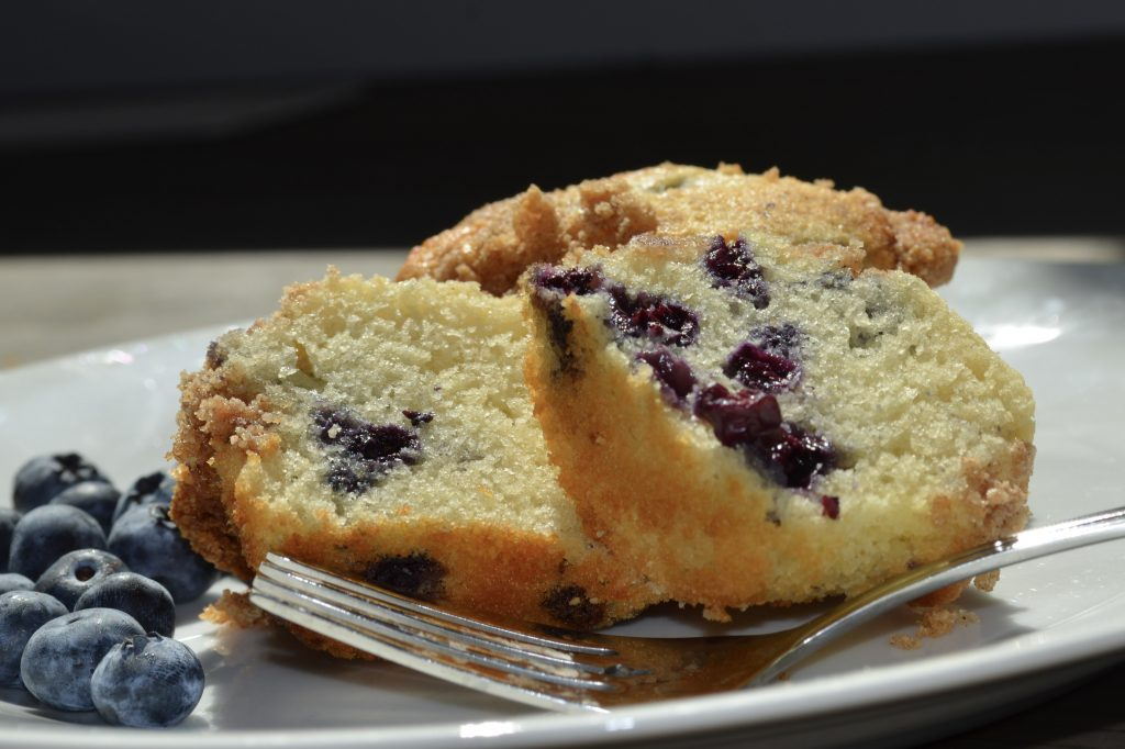 Two muffin halves with dark blue blueberries and a silver fork.