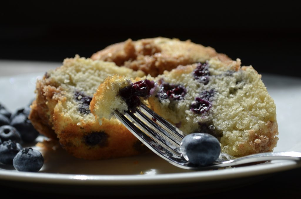 Two blueberry muffins on a white plate with blueberries on the side. A fork holding a piece of the muffin and a blueberry.