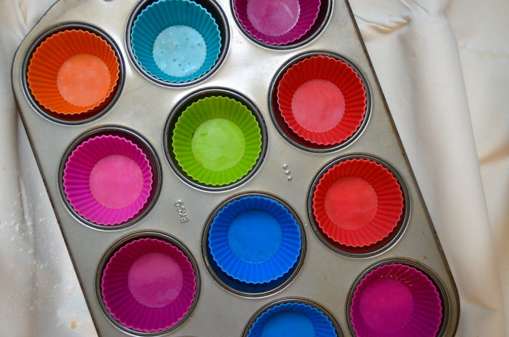 A muffin tin lined with colourful silicon muffin liners.
