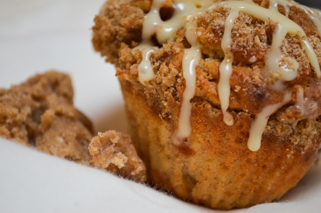 Apple Pie muffin with a brown crumble and white crosses of icing.