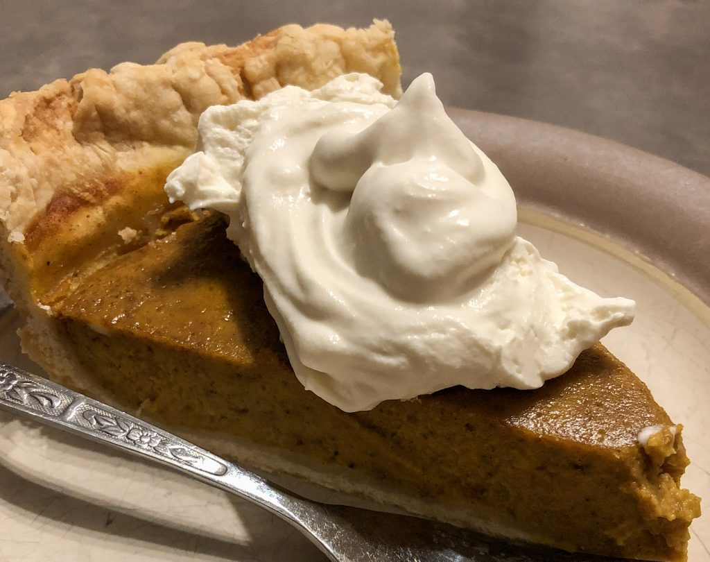 A warm brown slice of pumpkin pie with fluffy whipping cream and a fork on the side.
